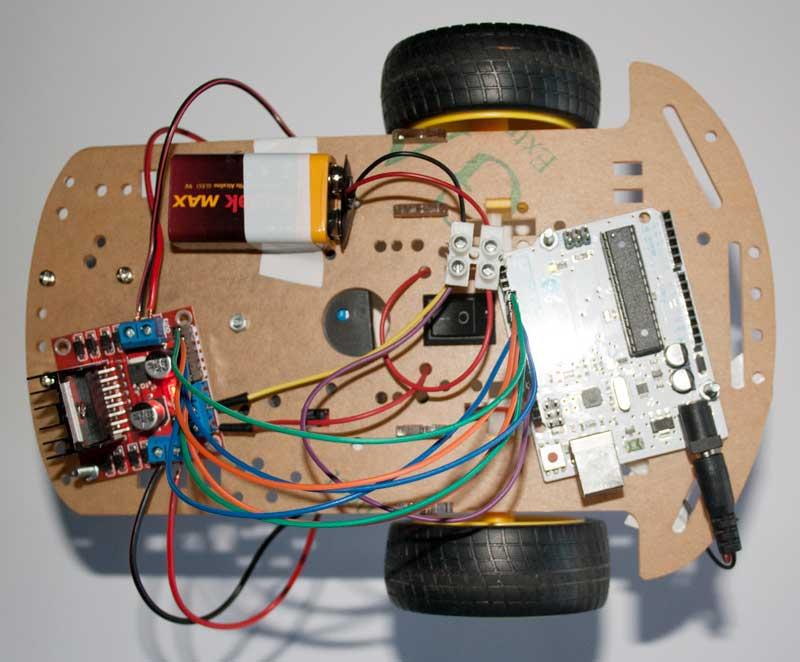 Chasis completo con la placa Arduino, controlador L298N, portapilas, y pila de 9V.